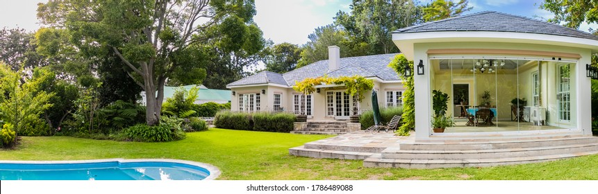Cape Town, South Africa - February 6, 2020: Wide angle view of Exterior of Upmarket wealthy suburban mansion house with landscaped garden and swimming pool
