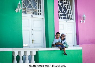 Cape Town / South Africa - January 1, 2010: A young boy and woman outside a home on the colorful Bo Kaap streets of the Malay Quarter of Cape Town, South Africa.