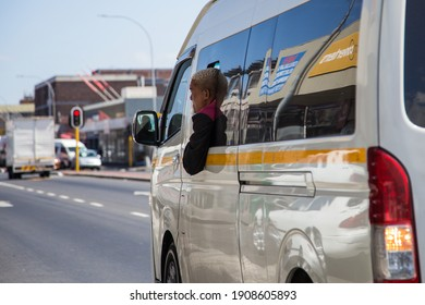 Cape Town, South Africa - January 2021: South African Taxi guard riding with head outside of Minibus Taxi.