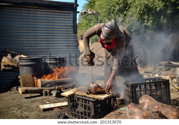 CAPE TOWN, SOUTH AFRICA - JANUARY 26, 2013: African woman processes sheep's heads (so called Smileys) for a meal in Langa town ship