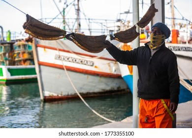 CAPE TOWN, SOUTH AFRICA – JULY 4: Fisherman selling local delicacy, bokkoms (dried fish) in Kalk Bay Harbour