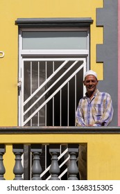 Cape Town, South Africa. March 2019. Man stands outside house and looks straight to camera in the Malay Quarter, Bo-Kaap, historical area of brightly painted houses, housing largely Muslim families.