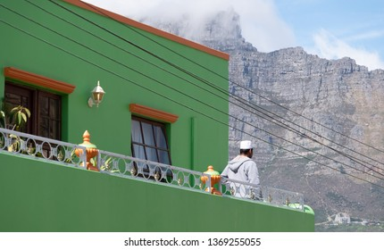 Cape Town, South Africa. March 2019. Man stands on the balcony of his house in the Malay Quarter, Bo-Kaap. Table Mountain can be seen behind.