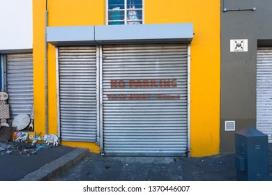 Cape Town, South Africa - March 21, 2019:  metal roller shutter garage door in the city street with the words no parking tow away zone painted in red paint as a warning to not park there