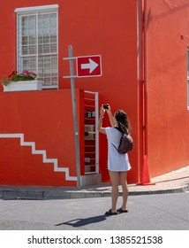 Cape Town, South Africa, March 2019. Girls in white dress photographs bright orange house in the Malay Quarter, Bo-Kaap, Cape Town. Historical area of brightly painted houses in the city centre.