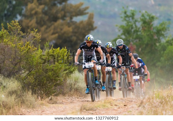 Cape Town, South Africa - March 25, 2018:  mountain bikers or cyclists follow behind one another down a hillside on a mountain track during the Absa Cape Epic international cycle tour on the final leg