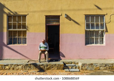 CAPE TOWN, SOUTH AFRICA - MAY 3, 2018: Senior man sitting and reading a book in the famous malay quarter of Bo Kaap, known for its colorful architecture in Cape Town.