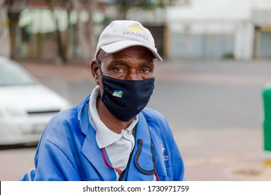 Cape Town, South Africa - May 2020: African Elderly Male/Cleaner Sanitizing Shopping carts/trolley  wearing face mask during Corona Virus Pandemic in Africa. Poverty, Minimum Wage, Front line worker.