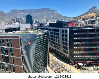 Cape Town, South Africa - November 18, 2018: The Cape Town waterfront with PWC offices and Radisson hotel overlooked by Table Mountain and Lions Head