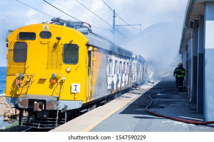 Cape Town, South Africa - October 7, 2019: Firefighter extinguishing burning train in arson attack on railway transport service. Investigations are being made as attacks effect transportation.