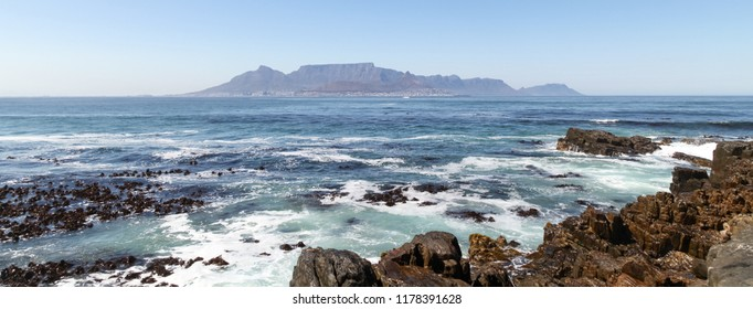 Cape Town, South Africa. Panorama of Table Mountain on the horizon, Photographed from Robben Island where Nelson Mandela was imprisoned. Rocks in foreground.