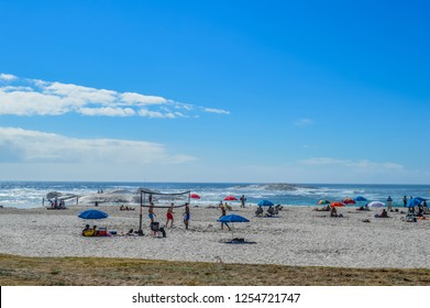 Cape Town, South Africa - Sep 17 2018:People relaxing and taking sun bath on white sands of  Camp's bay beach