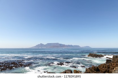 Cape Town, South Africa. View of Table Mountain on the horizon, Photographed from Robben Island where Nelson Mandela was imprisoned. Rocks in foreground.