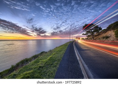 Cape Town sunset over ocean and road to the right with cars passing by shown with colorful streaks of light