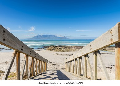 Cape Town, Table Mountain across the ocean from wooden stairs on Blouberg beach