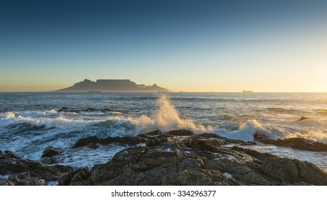 Cape Town Table Mountain's iconic flat top seen from Blouberg Strand in South Africa during sunset.