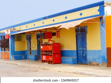 CAPE VERDE ISLANDS, AFRICA - December 23, 2017. Outside front view of small convenience grocery store and mini market, bright blue yellow colors in neighborhood street of traditional village.