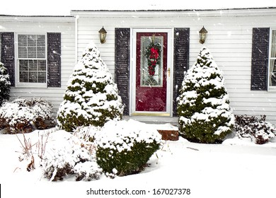 Cape-cod style home with front red door and wreath for the holidays in the midst of a snowstorm.