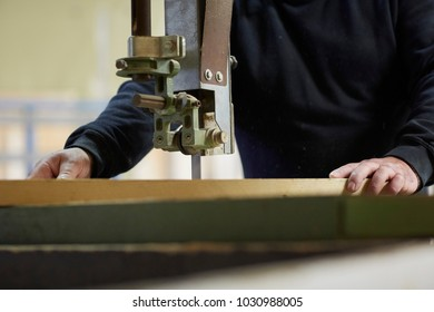 Capenture man  close up sawing wood with a machine in a factory