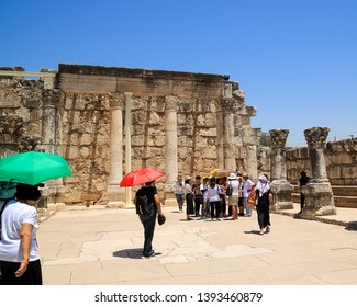Capernaum / Israel - 6/8/17: Group of tourists gather at the archaeological ruins of a synagogue at the town of Capernaum in Israel