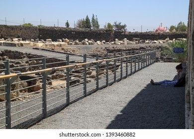 Capernaum / Israel - 6/8/17: Woman sitting on the ground and reading at the archaeological ruins of the town of Capernaum in Israel