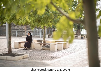 Capernaum, Israel - December 21 2017: A sister is meditating at the site of Capernaum Synagogues.