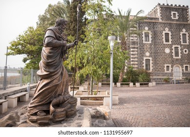Capernaum, Israel - December 21 2017: Statue of St Peter next to the ruin of Capernaum Synagogues.