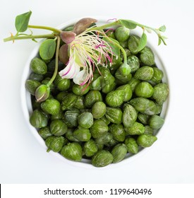 Capers in bowl on white, top view. Caper with green leaves and flower on white background