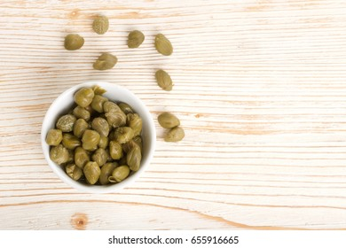 capers in bowl on wooden background