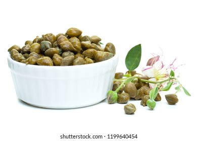 Capers with caper flowers in white bowl on white background