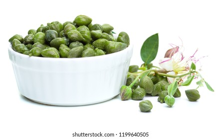 Capers, green leaves and caper flower in white bowl on white background