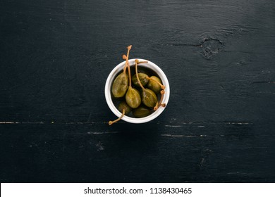 Capers on a black wooden background. Top view. Free space for your text.