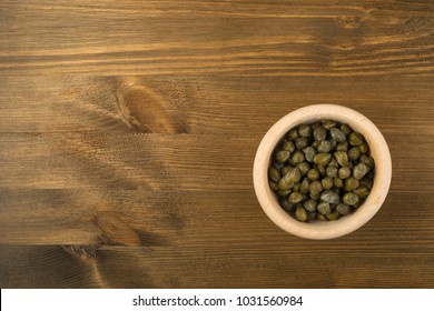 Capers Pickled in Vinegar and Salt. Green Marinated Caper in Wooden Bowl Top View