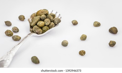 Capers in a spoon isolated on a white background. Bunch canned pickled or salted capers.