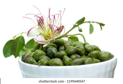 Capers in white bowl isolated on white. Caper with green leaves and flower on white background