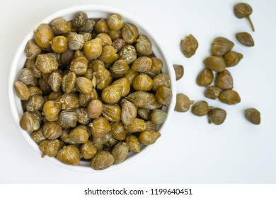 Capers in white bowl on white background, top view