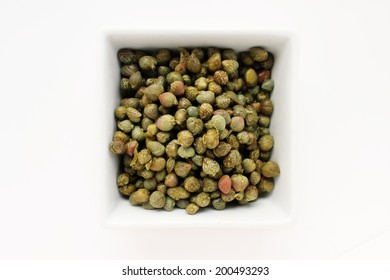 capers in white dish isolated on white background