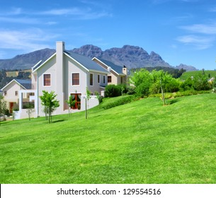 Cape-style house against blue misty mountains. Shot in Western Cape, South Africa.