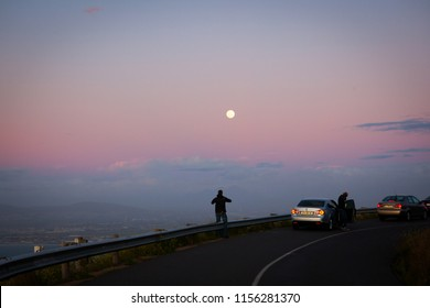 Capetown, South Africa - September, 2015. Tourists stopped on the road to shoot the amazing sunset panorama and full moon above Capetown on their way from Lion's Head