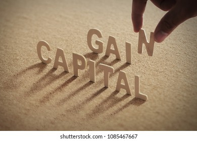 CAPITAL GAIN wood word on compressed or corkboard with human's finger at N letter.