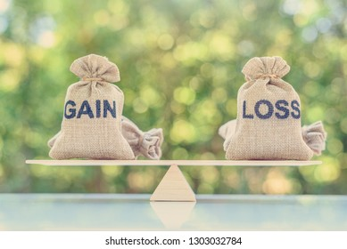 Capital investment gain and loss, financial concept : Gain and loss bags on a basic balance scale, depicts balancing between profit and loss while managing assets e.g bonds, stocks, derivatives, ETFs