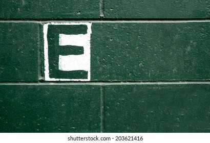 The capital letter E painted over white on a textured green brick wall.