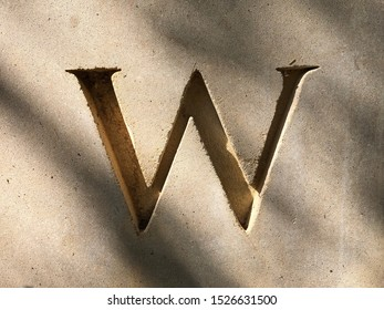 Capital letter W cutout in concrete wall surface, typography, serif alphabet, embossed character