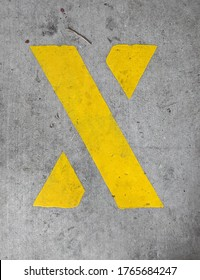 Capital letter X in yellow stencil paint on concrete