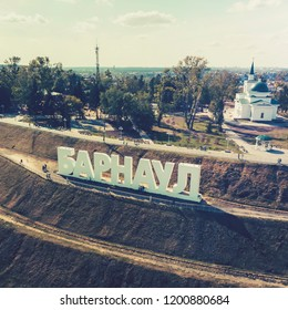 capital letters on the stepped hill spelling out a Russian city's name BARNAUL. Gigantic sign of city's name installed on the staged upland. Set up letters of city name in the touristic zone