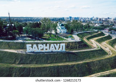 capital letters on the stepped hill spelling out a Russian city's name BARNAUL. Set up letters of city name in the touristic zone