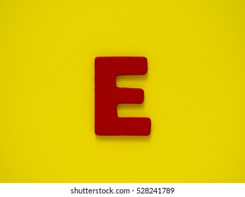 Capital red letter E from wood on yellow background. Alphabet vowel.