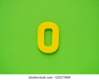 Capital Yellow letter O from wood on green background. Alphabet vowel.