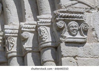 Capitals over a side door of the cathedral of Venzone decorated with floreal pattern reliefs and a human figure