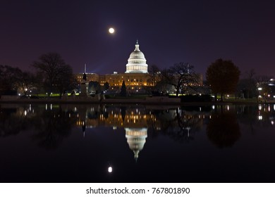 Capitol Hill panorama at night during super moon. Calm water of the pool with reflection of the dome.